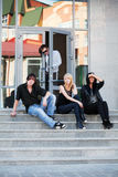 Group of young fashion people sitting on the steps Stock Images