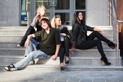 Group of young fashion people sitting on the steps Royalty Free Stock Image