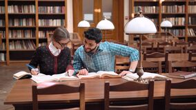 Teens Students in Library. Two smiling students reading books together, smart fair-haired girl in glasses taking notes into notebook, intelligent bearded man stock video
