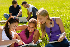 Teens studying in park reading book students Stock Photos