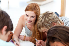 Teens studying together lying on the floor Stock Images