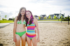 Teens in summer fun sun. Two young girls in swimwear and bikini on a sandy beach standing together smiling at camera Royalty Free Stock Photo