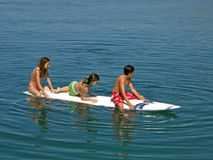 Teens on surf desk. Summer fun. View at a boy and girls sitting on surfing desk - floating and enjoying at summer holidays - vacation in Adriatic sea (Croatia Stock Image