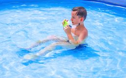 Teens are swimming in the pool. Swimming children bathing fun playing girl with circle boy in mask for swimming hot summer day under the open sun Stock Images