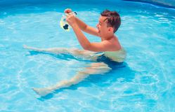 Teens are swimming in the pool. Swimming children bathing fun playing girl with circle boy in mask for swimming hot summer day under the open sun Stock Photos