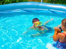Teens are swimming in the pool. Swimming children bathing fun playing girl with circle boy in mask for swimming hot summer day under the open sun Stock Photography