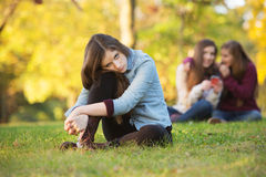 Teens Talking About Girl. Lonely girl leaning on knee in front of teenagers talking Royalty Free Stock Photography