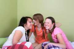 Teens telling secrets. Three teenage girls have a slumber party or sleepover and one is whispering secrets in the other's ear Stock Photography
