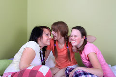 Teens telling secrets. Three teenage girls have a slumber party or sleepover and one is whispering secrets in the other's ear Stock Photos