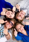 Teens With Thumbs Up. Four young friends lying down showing thumbs up sign Royalty Free Stock Photos