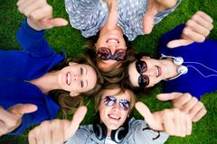 Teens With Thumbs Up. Four young friends lying down showing thumbs up sign Stock Image