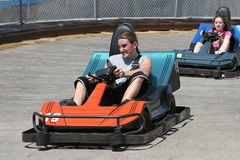 Teens At The Track. Two teenagers racing go carts Stock Photo