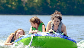 Teens Tubing Behind a Boat Royalty Free Stock Photos