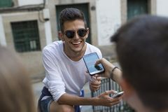 Teens using cell phones. Portrait of young male teen smiling using cell phone outdoors with friends Royalty Free Stock Image