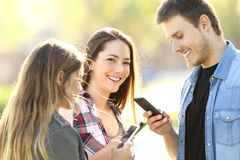 Teens using smart phones and one looking at you. Three teens using their smart phones and one of them looking at you in the street Royalty Free Stock Photography