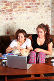Teens working on computer. Two brunette teenage girls sitting on a couch in their pajamas while searching or working on a computer networking Stock Photo