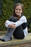 Teeny with striped socks. Teenager girl with black and white striped socks sitting on a wall in the gaerden Stock Images
