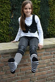 Teeny with striped socks. Teenager girl with black and white striped socks sitting on a wall in the gaerden Stock Photos