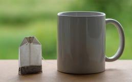 Teepaket und ein Becher Stockfoto