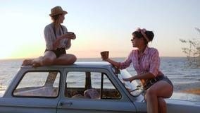 Teeparty von schönen Mädchen zur Autohaube auf Damm im Sonnenuntergang, Freundinnen, die Tee trinken stock video