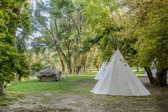 Teepee and cabin in forest of trees Stock Photo