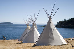 Teepee Camp By Water. Three teepees (aka tipis) are lined up in a row in front of water. These teepees are used at a summer camp. Teepees were one form of stock photo