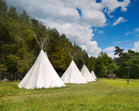 Teepee Camp, Wigwam. Teepees camp on a meadow surrounded by forest royalty free stock photo