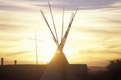 Teepee and cross silhouette on Indian reservation stock photography