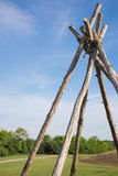 Teepee frame, bound with rope. Teepee frame, made with seven long trees and bound with rope, sits in a field next to a mound. A blue sky and a few thin, white Royalty Free Stock Image