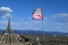 Teepee Frame and US Flag. With mountains and blue sky in background Royalty Free Stock Image