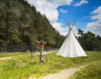 Teepee, Wigwam, Totem. Canvas teepee and totem on a meadow surrounded by forest Royalty Free Stock Photography