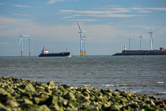 Tees Estuary, Middlebrough, Cleveland, england. A ship entering the Tees Estuary with a backdrop of the sea wind turbines near the entrance to the harbour Royalty Free Stock Photography