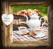 Teesatz im Garten im Holzrahmen mit Herzen Stockfotografie