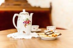 Teesatz mit bisquits auf Holztisch lizenzfreie stockfotos