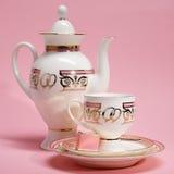 Teesatz mit Süßigkeit auf rosa Hintergrund Stockbild