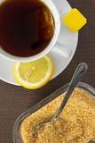 Teeschale, brauner Zucker und Scheibe der Zitrone Stockbilder