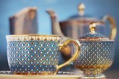 Teeschale fünf Farben der thailändischen schönen Kunst traditionelle (Bencharong) über blauem undeutlichem Hintergrund Stockfotos