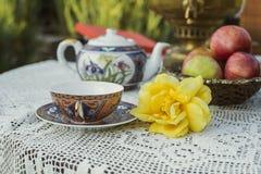 Teeschale, Gelbrose, Äpfel und Samowar Stockfotografie