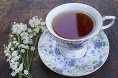 Teeschale, Maiglöckchen, auf hölzernem Hintergrund Stockbilder