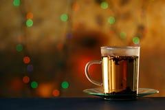 Teeschale mit dem Teeblatt, das auf dem dunkelblauen bunten Hintergrund der Tabelle und der Unschärfe rausschmeißt Stockfotos