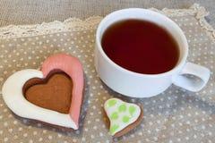 Teeschale mit geformtem Keks des Herzens Lizenzfreies Stockfoto