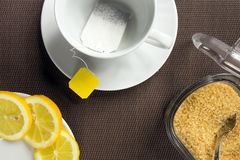 Teeschale, Scheiben der Zitrone und brauner Zucker Stockbilder