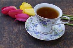 Teeschale, Tulpenblume, auf hölzernem Hintergrund Stockbild