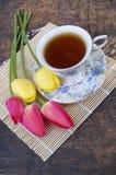 Teeschale, Tulpenblume, auf hölzernem Hintergrund Lizenzfreie Stockbilder