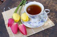 Teeschale, Tulpenblume, auf hölzernem Hintergrund Lizenzfreies Stockfoto