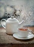 Teeschale und Teekanne mit an eisigem Tag des Winters Stockfotografie