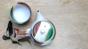 Teeschalen mit Teekanne auf altem Holztisch Lizenzfreies Stockfoto