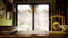 Teeshop verwischte Hintergrund, hölzerne Stange, Tischplatte Traditionelle Zeremonie, Klingel mit chinesischen Hieroglyphenwünsch Lizenzfreie Stockfotografie