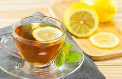 Teet med mintkaramellen och citronen på wood bakgrund, varm toning, selecti Royaltyfri Fotografi