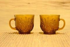 Teetassen auf einem mit Ziegeln gedeckten Hintergrund Stockbild